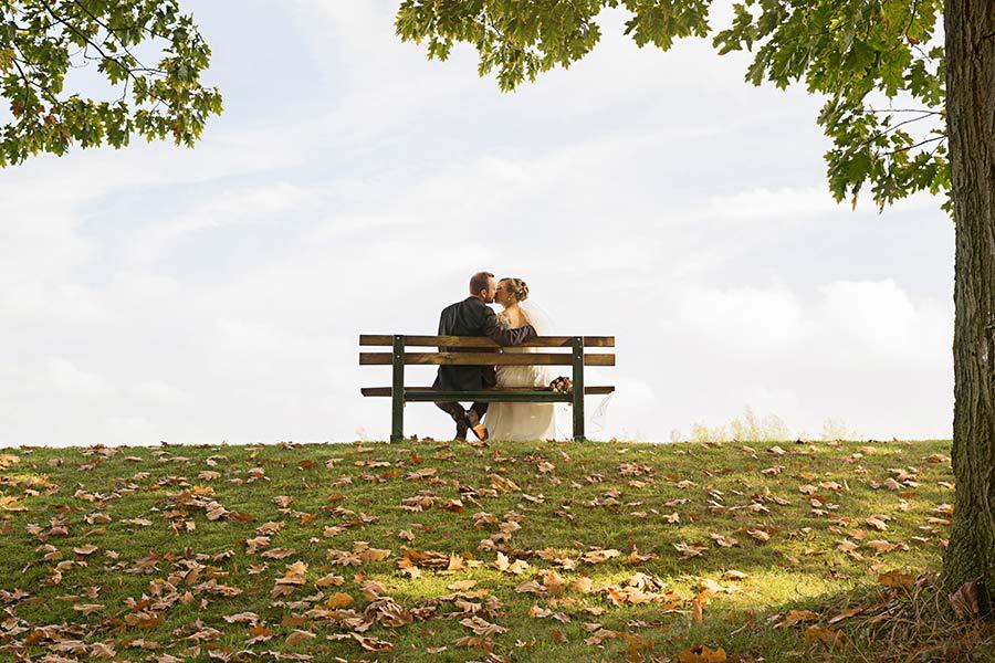 Hochzeitspaar auf Bank im Park